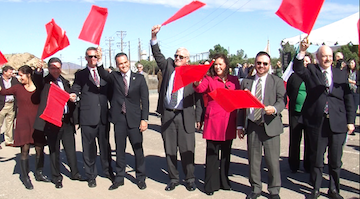 U.S. and Mexico officials wave flags to signal the beginning of construction on a $700 million border infrastructure project in Otay Mesa. Photo/Susan Murphy.