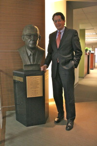 Craig Higgs stands next to bust of his father and founding partner, Dewitt 'Dutch' Higgs.