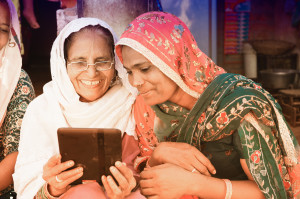 Women from India use their tablet to connect with family over social networks.