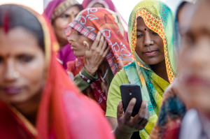 An Indian woman uses her smartphone to track and manage information.