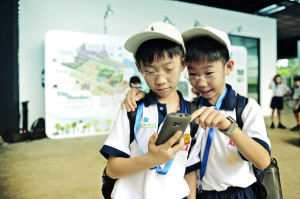 Twin brothers from Singapore teach each other how to access a next-generation mobile learning platform from the We Learn program.