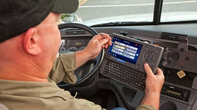A truck driver uses one of Omnitracs' mobile applications. Photo courtesy Omnitracs