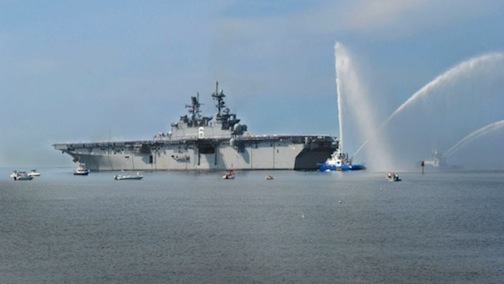 The future amphibious assault ship USS America is saluted as it departs Huntington Ingalls Shipbuilding in Pascagoula, Miss. (Navy photo)