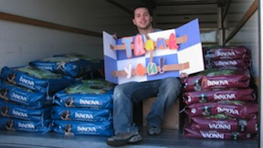 A San Diego PAWS volunteer with donated dog food.