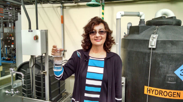 Halla Razak, director of public utilities for the city, with pure recycled water. (Photo by Chris Jennewein)