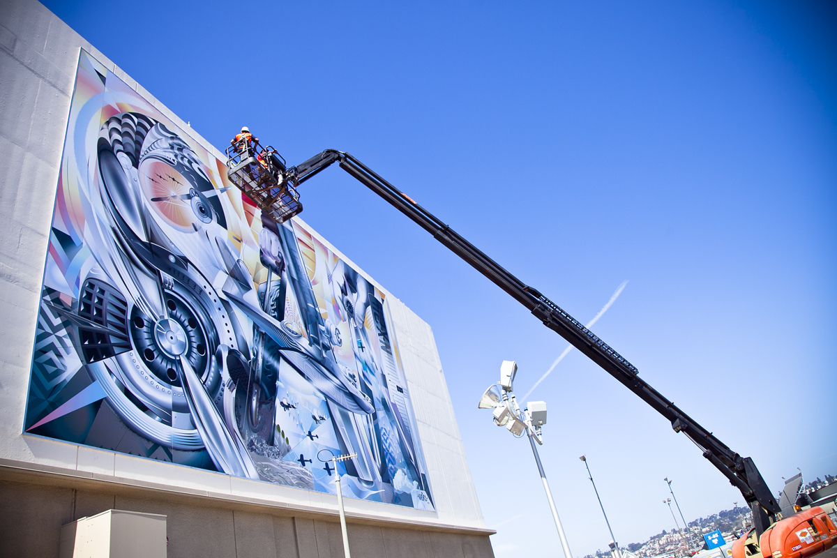 Hoisting the mural by Jari 'Werc' Alvarez on the wall of the Commuter Terminal.