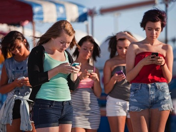 Girls absorbed with smartphones