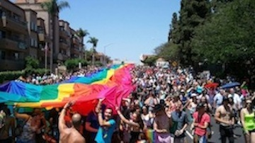 The San Diego Pride rainbow flag is unfurled on University Avenue in Hillcrest. (Photo courtesy of San Diego Pride.)