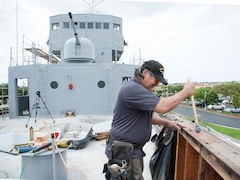 Workman on the deck of the USS Recruit during refurbishment event on Veterans Day.