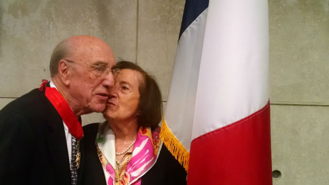 Dr. Roger Guillemin receives a kiss from his wife, Luciene, after receiving the award. (Photo by Chris Jennewein)