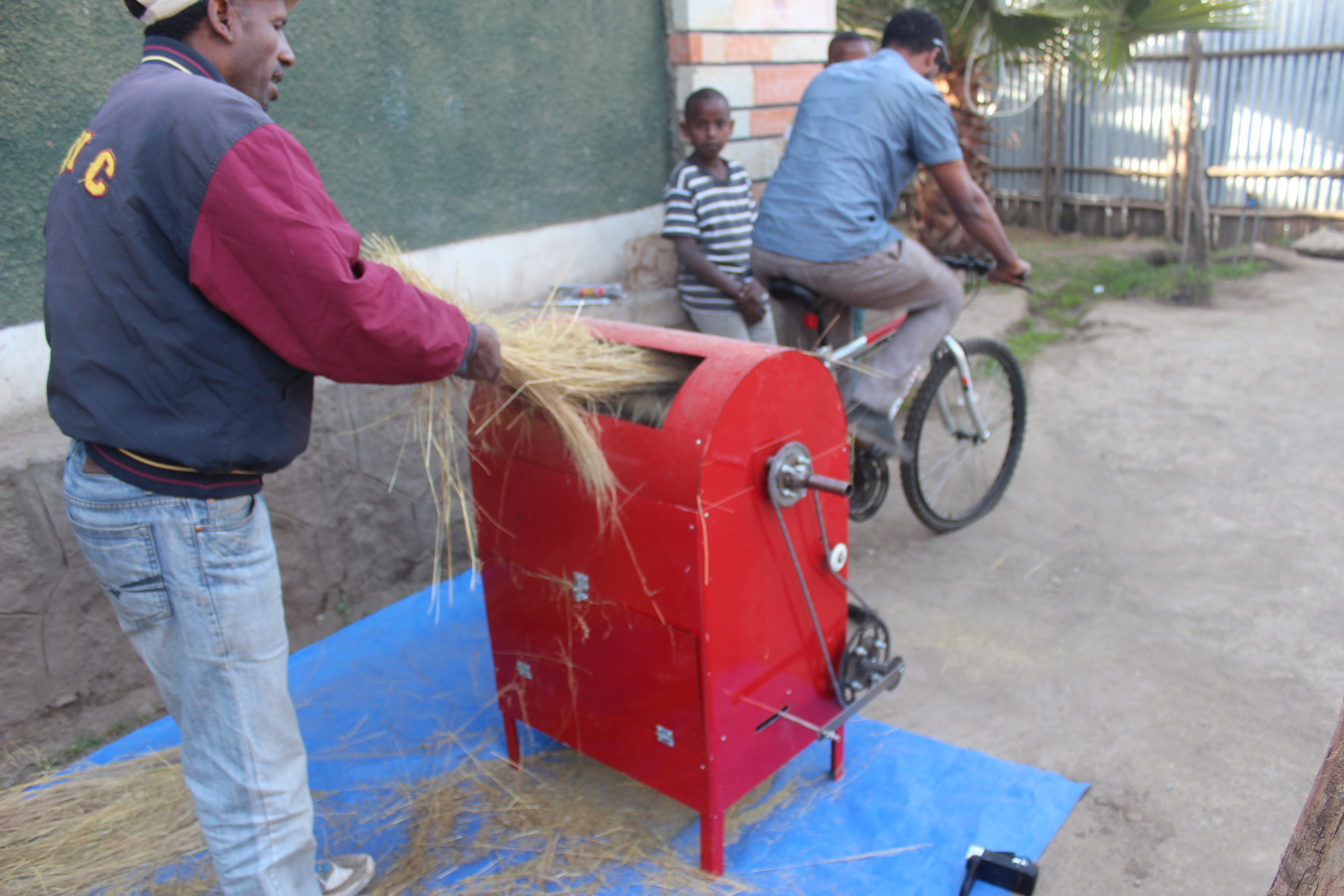 Ethiopians using the first prototype of the threshing machine powered by a bicycle.