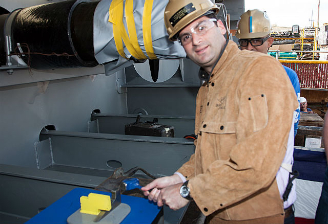 Eric Fabrikant hammers the initialed plate onto the ship's keel.  (Courtesy NASSCO)