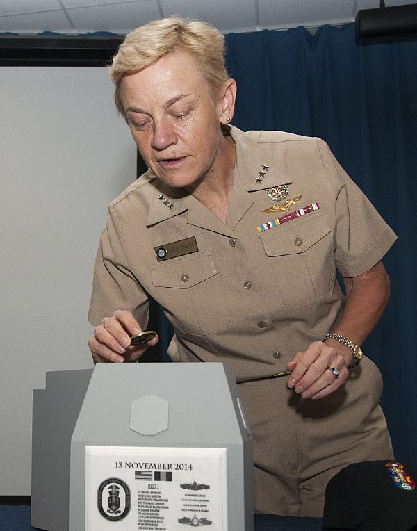 Vice Adm. Nora Tyson, deputy commander of U.S. Fleet Forces Command, places a coin inside a time capsule during an Aegis Ashore Romania mast stepping ceremony at Tactical Training Group, Atlantic at Naval Air Station Oceana in Virginia Beach, Va.