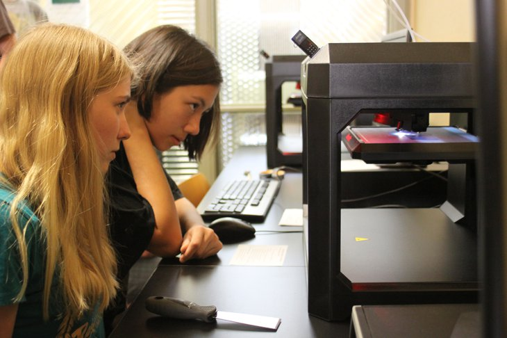 Jeanne Walker and Eleanor Sailor are captivated by the 3-D printer process.