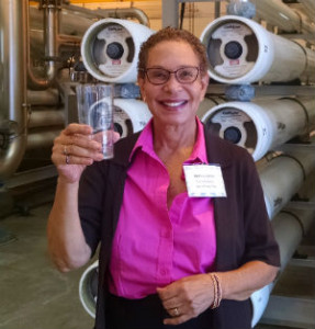 Councilwoman Patricia Aguilar holds a glass in front of the reverse-osmosis filters.