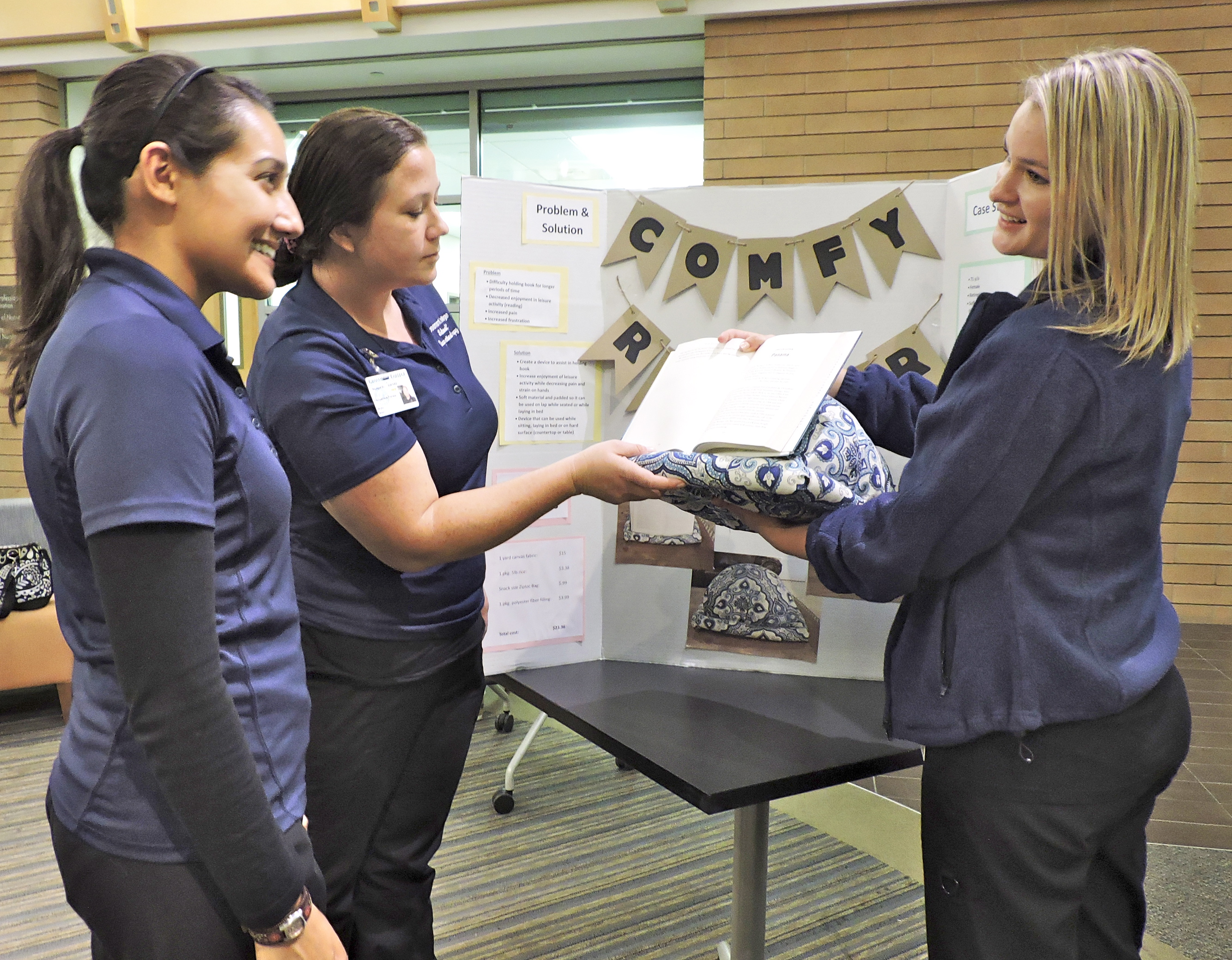 Amanda Plascencia, right, explains the benefits of the Comfy Reader, a book rest she created for her grandmother, whose osteoarthritis has affected her ability to hold books while reading. From left are fellow OTA students Patricia Cerda and Shylo Allen.