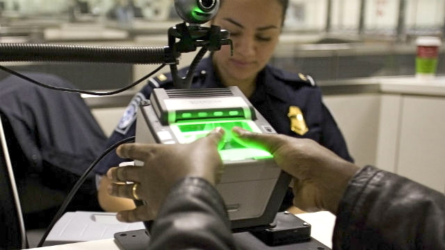 A Customs and Border Protection officer uses a fingerprint scanner.