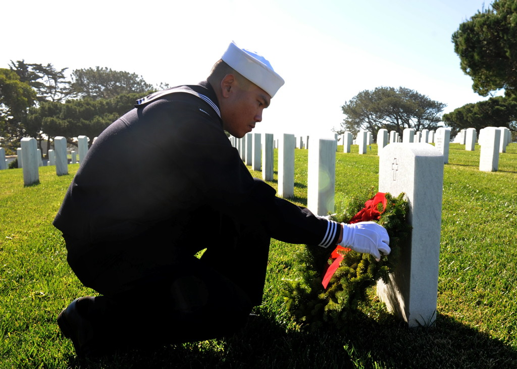 Hospital Corpsman 2nd Class Marlon Yulo, assigned to Naval Medical Center San Diego, places a wreath on a headstone during the 23rd annual Wreaths Across America Ceremony at Fort Rosecrans National Cemetery on Point Loma. In its 10th year of participation, Fort Rosecrans laid down 4,600 wreaths for fallen service members. (U.S Navy Photo by Mass Communication Specialist 2nd Class Kyle Carlstrom)