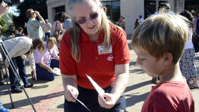 Marit Resnik, a senior science educatorat Reuben H. Fleet Space Center, teaches a young boy how to see the eclipse using a pin hole. (Photo by Chris Stone)