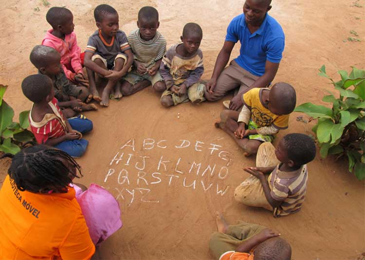 Two Peace Corps volunteers practicing the alphabet with children in Mozambique. (Courtesy UC San Diego)