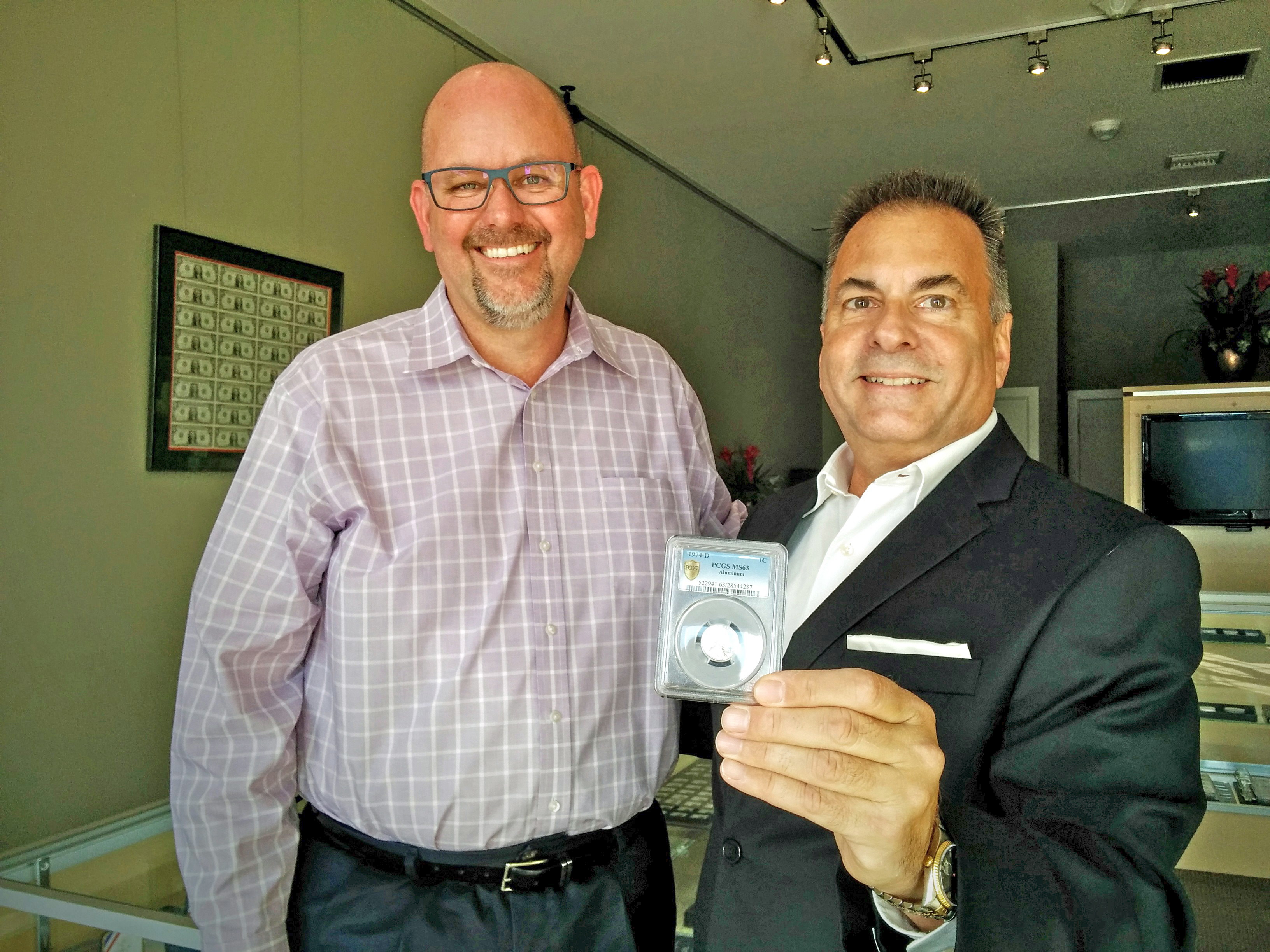La Jolla Coin Shop Owner Michael McConnell and real estate agent Randy Lawrence of Berkshire Hathaway display the 1974-D aluminum penny.