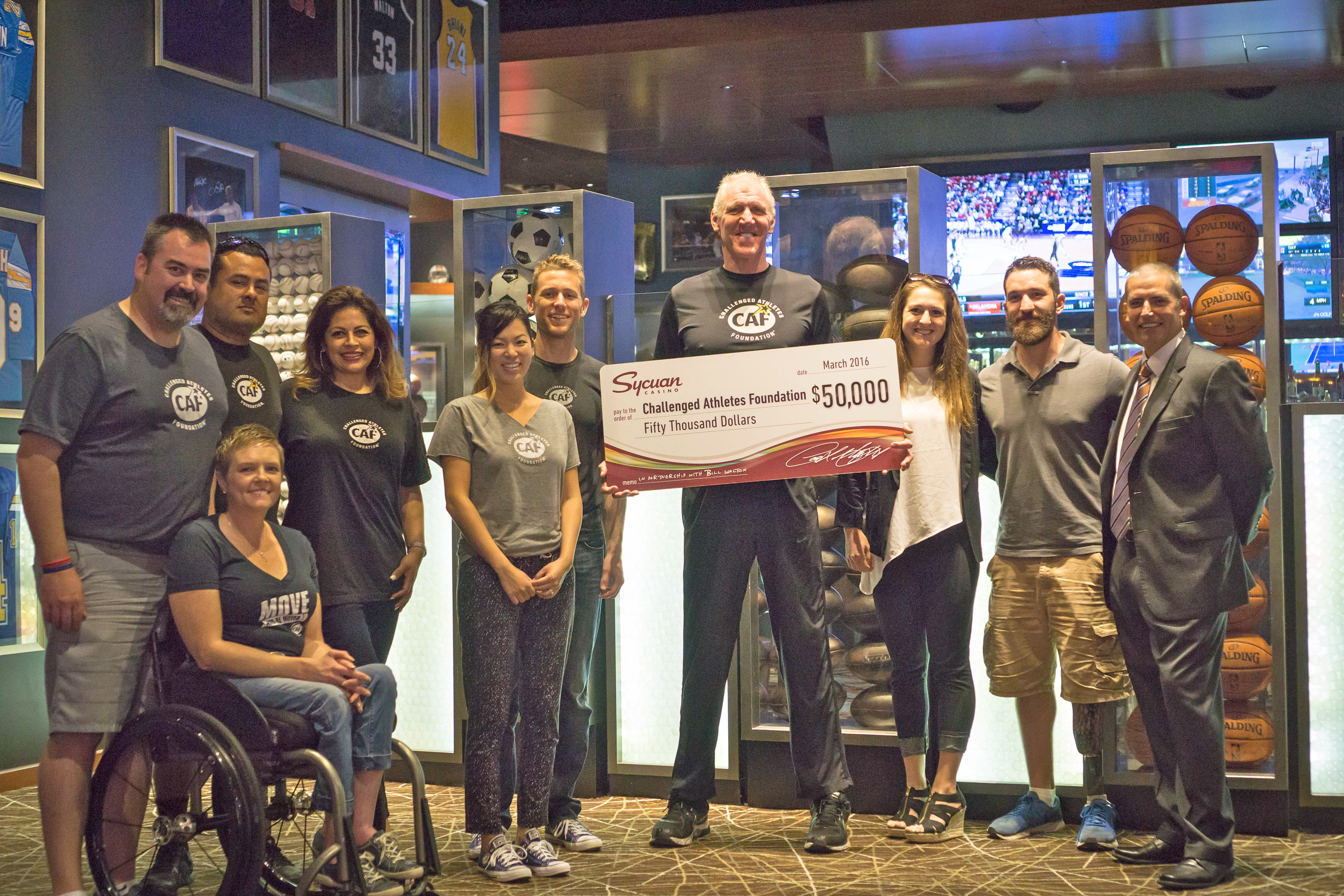 Bill Walton (center) and representatives of the Challenged Athletes Foundation accept a $50,000 donation presented by Sycuan Casino's general manager, John Dinius, right.