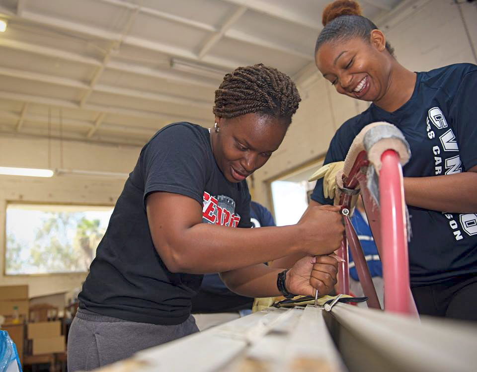 Sailors Brenda Taylor, left and Shelby Woodson, both assigned to the USS Carl Vinson, remove hinges from a door at ReStore in Mission Valley. (U.S. Navy photo by Mass Communication Specialist 3rd Class Zackary Alan Landers)