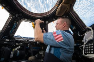 NASA Commander Barry (Butch) Wilmore shoots a scene with the IMAX camera through the window of the International Space Station's Cupola Observation Module.