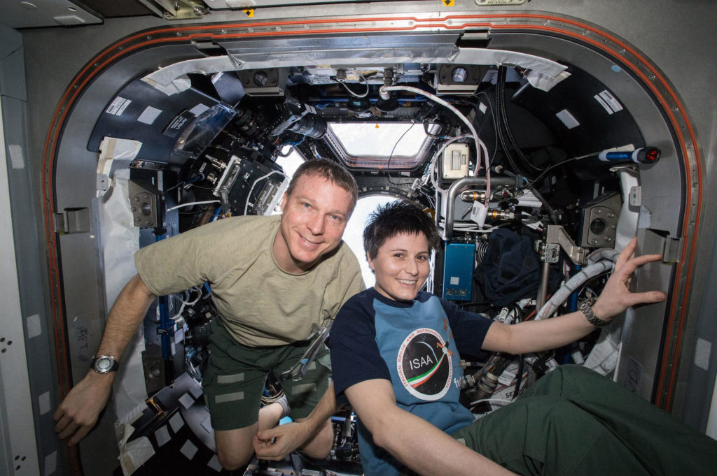 NASA Commander Terry Virts and European Space Agency astronaut Samantha Cristoforetti smiling after her haircut, by Terry.