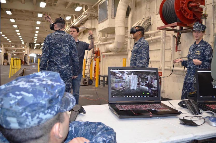 SPAWAR military and civilian employees assist sailors during a virtual reality demonstration on board the amphibious transport dock ship USS Anchorage. The week prior, three-dimensional images were produced during a ship scan event of various shipboard spaces on Anchorage. (U.S. Navy photo by Dawn Stankus)