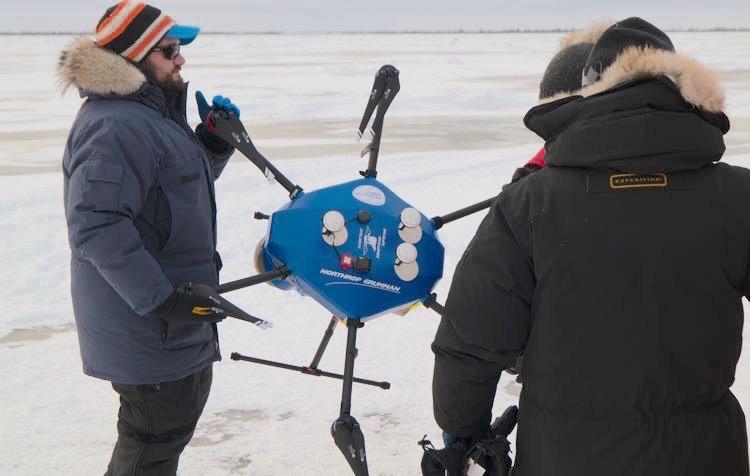 Operation #PolarEye team members walk their custom hexacopter to the launch site on the Hudson Bay. (Credit: Northrop Grumman)